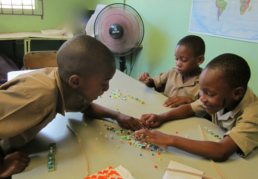 Students practice spelling their name with letter tiles and alphabet beads